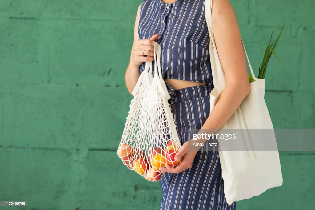 Female hands with shopping cotton mesh eco bag on green background. Zero waste concept : Stock Photo