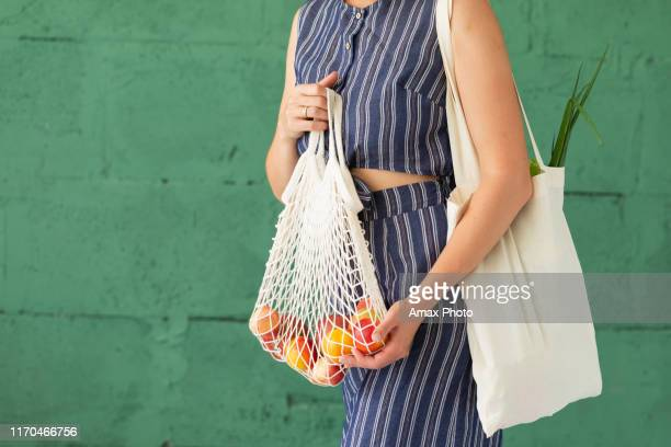 female hands with shopping cotton mesh eco bag on green background. zero waste concept - environmental issues stock pictures, royalty-free photos & images