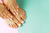 Female hands with white manicure and pedicure on pink and blue background, top view