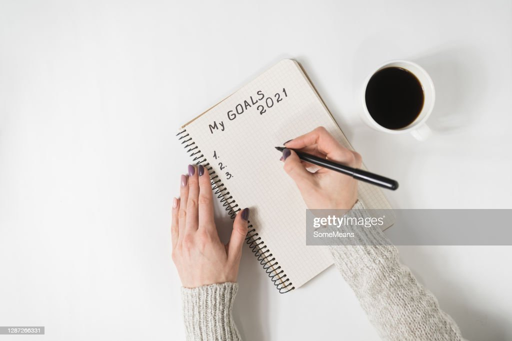 Female hands writing My Goals 2021 in a notebook. Mug of coffee on the table, top view : Stock Photo