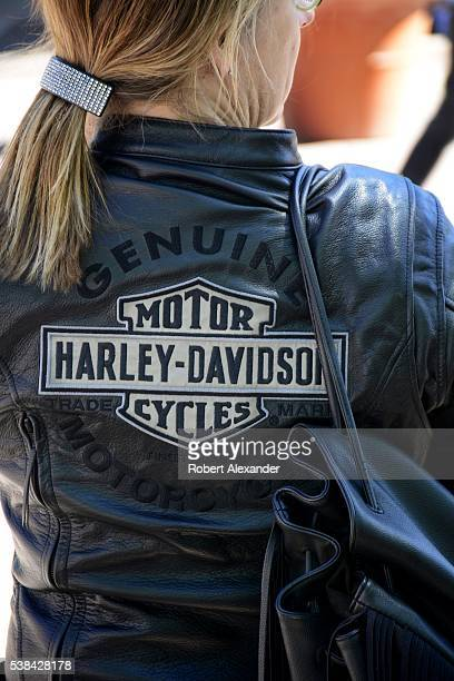A female HarleyDavidson motorcycle enthusiast watches a lowrider custom car parade through Santa Fe New Mexico on May 22 2016
