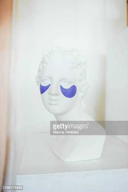 female head sculpture with cosmetic patches under the eyes. - cerimônia - fotografias e filmes do acervo