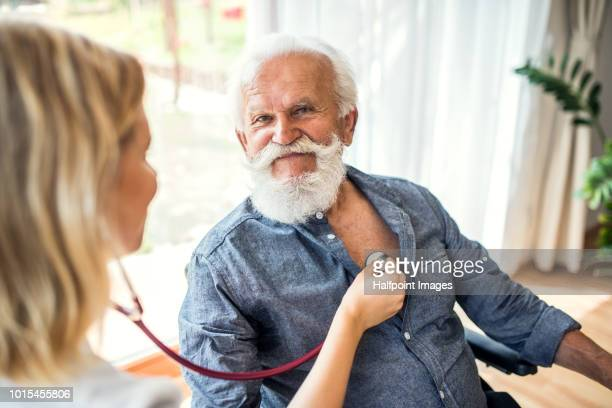 female health visitor examing a senior man in a wheelchair during home visit. - woman flat chest stock photos and pictures