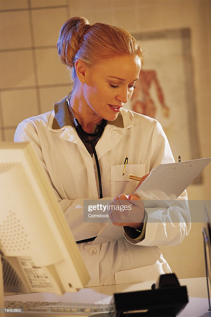 Female healthcare professional making notes on chart : Stockfoto