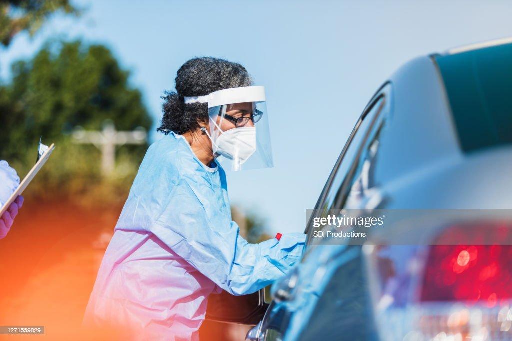 女性医療従事者がCOVID-19を車の運転手に管理 : ストックフォト