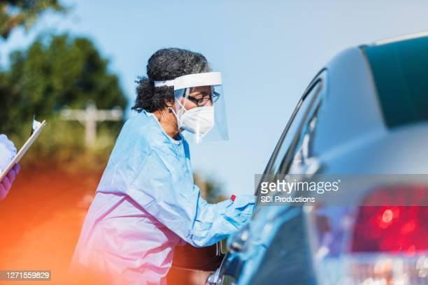 女性医療従事者がcovid-19を車の運転手に管理 - ドライブスルー検査 ストックフォトと画像