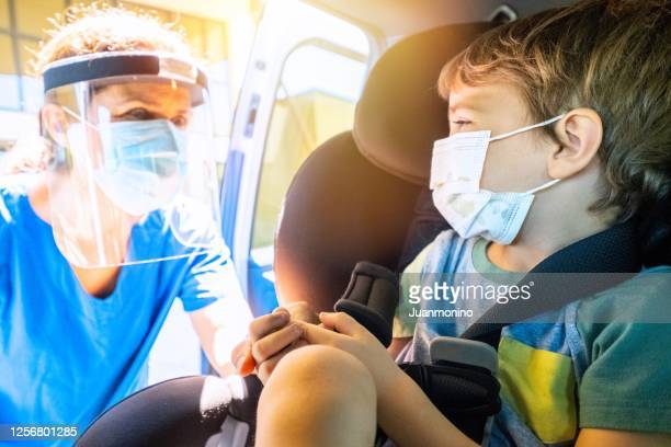 female healthcare worker approaching a child boy in order to perform a covid-19 test inside the car - coronavirus testing stock pictures, royalty-free photos & images