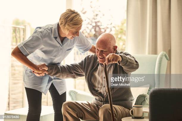 female healthcare worker supporting senior man at care home - infermiera foto e immagini stock