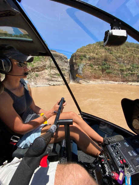 Female helicopter pilot flies above lake below Howick Falls