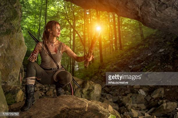 female heroine in cave entrance holding torch - warrior person stock photos and pictures