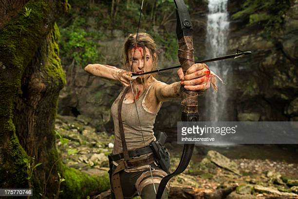 female heroine in the jungle hunting with bow and arrow - warrior person stock photos and pictures
