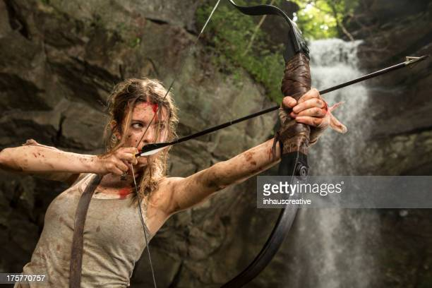 female heroine in the jungle hunting with bow and arrow - gunshot wound stock photos and pictures