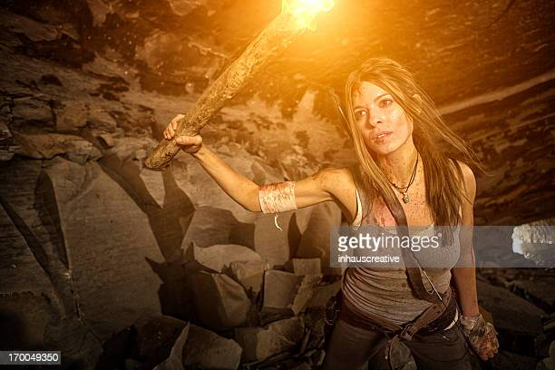 female heroine looking in a cave with torch - cave fire stock photos and pictures