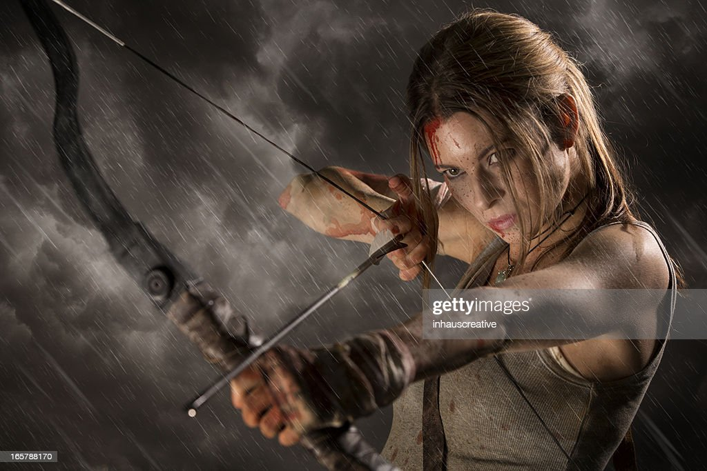 Female heroine with bow and arrow on a rainy night : Stock Photo