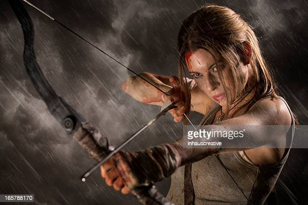 Female heroine with bow and arrow on a rainy night