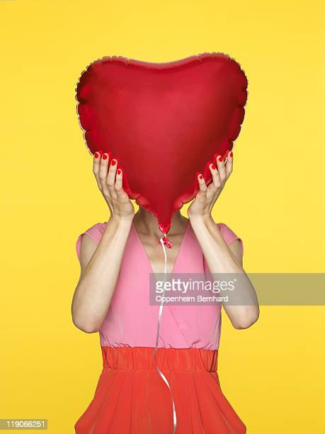 female hiding face behind heart shaped red balloon