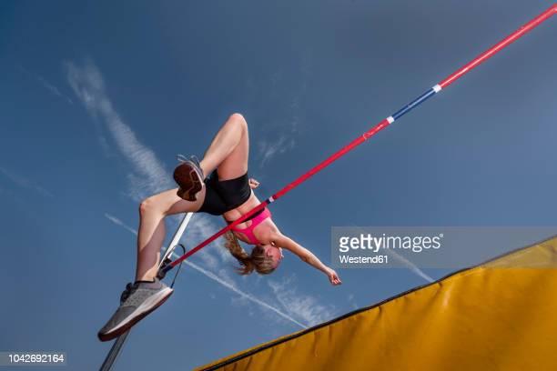 female high jumper, worm's eye view - atlete stockfoto's en -beelden