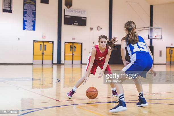 Female high school basketball player dribbling to hoop
