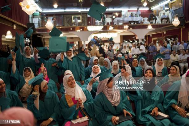 Female high school seniors celebrate and throw their caps into the air during their high school graduation ceremonies from the al Noor School June...