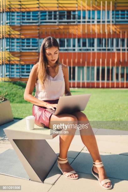female high school student at the campus using lap top - mulher saia curta imagens e fotografias de stock