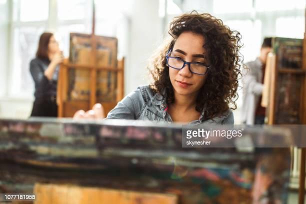 estudante de liceu feminino fazendo sua pintura em uma aula no estúdio de arte. - figurantes incidentais - fotografias e filmes do acervo