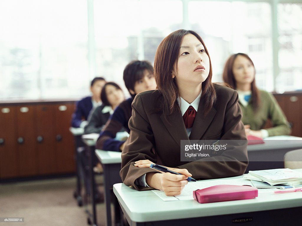 Female High School Student Sitting at a Table Looking Up : Stock Photo