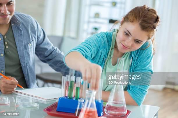 Weibliche High-School-Schüler verwendet Chemie zu Hause eingerichtet
