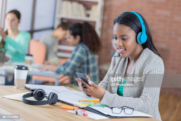 Female high school student wears wireless headphones in student lounge