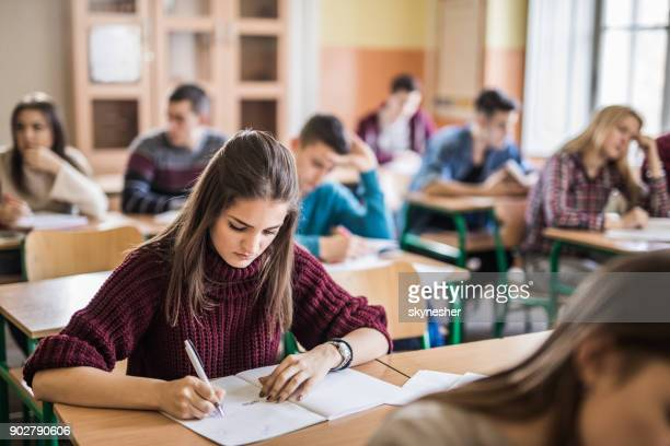 Female high school student writing a test in the classroom.