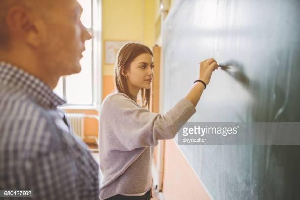 Vrouwelijke middelbare schoolstudent schrijven op schoolbord in de klas.