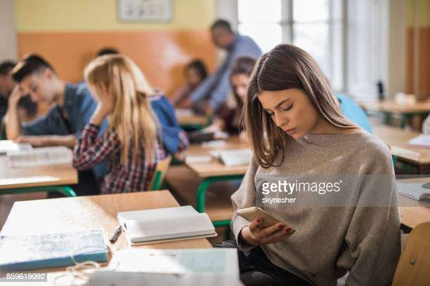 Female high school students using mobile phone during the class.