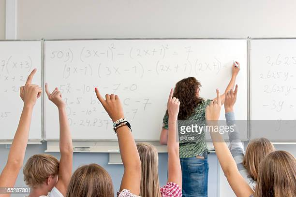 female high school teacher writing formula on whiteboard in classroom