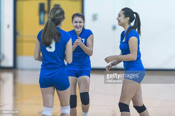 female high school volleyball teammates huddling together during a match - high school volleyball stock photos and pictures