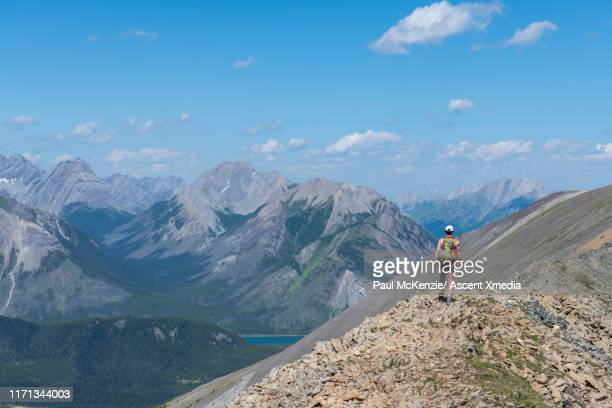 female hiker ascends to mountain ridge summit - ascent xmedia stock pictures, royalty-free photos & images