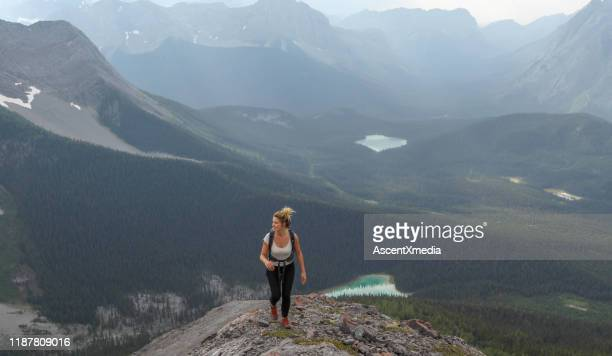 female hiker ascends to mountain summit - ascent xmedia stock pictures, royalty-free photos & images