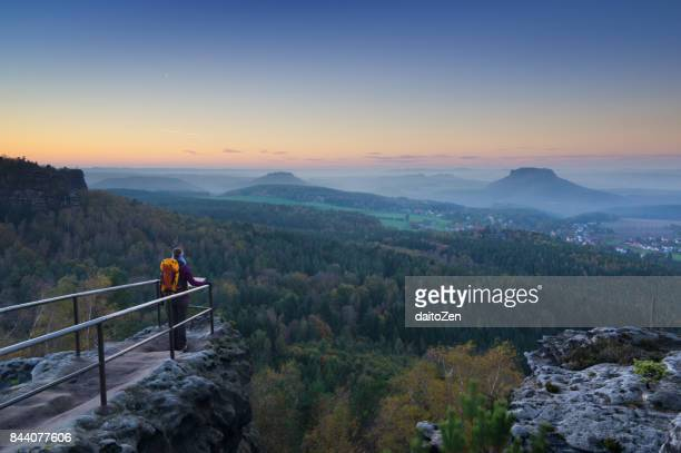 Female hiker at Papststein lookout with view over table mountains of Saxon Switzerland, taken after sunset, Saxony, Germany