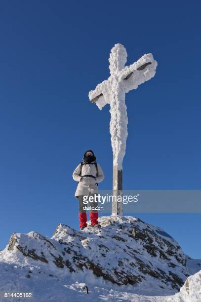 Female hiker at snow-covered summit cross on Great Arber, Bavarian Forest , Bavaria, Germany