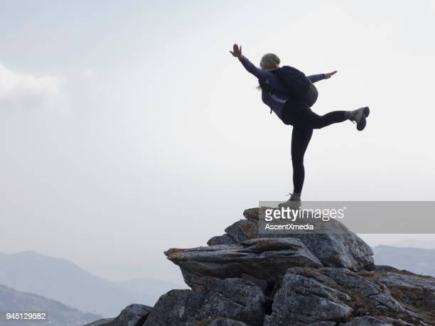 female hiker balances on one leg on pinnacle in mountains - human arm stock pictures, royalty-free photos & images