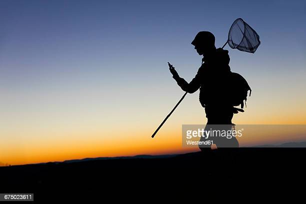 Female hiker carrying dip net and smart phone at dawn