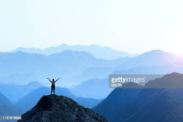 female hiker celebrating success - summit stock pictures, royalty-free photos & images