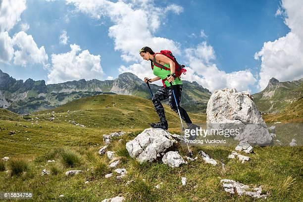 Female hiker climbing on the rock