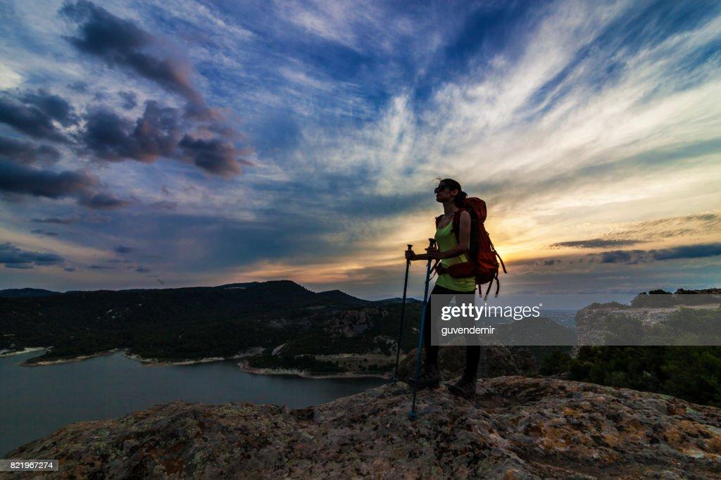 Female hiker climbing to mountain peak at sunset : Stock Photo