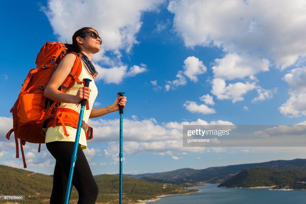 Female hiker climbing to mountain peak : Stock Photo