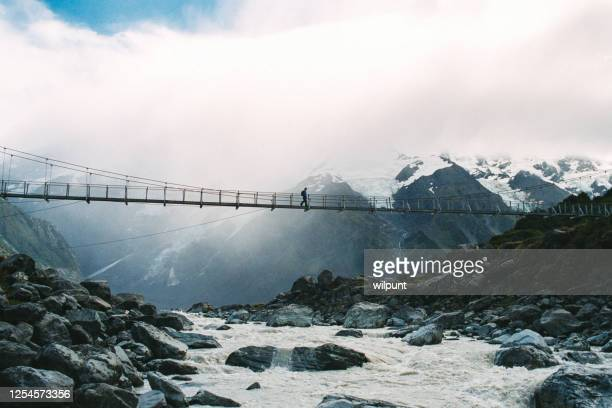 female hiker crossing a suspension bridge over a glacier river with snowcapped mountains and a glacier behind - suspension bridge stock pictures, royalty-free photos & images