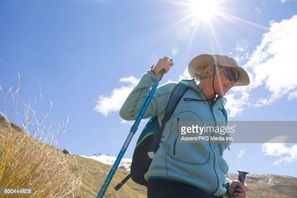 Female hiker descends from mountain summit, grasses