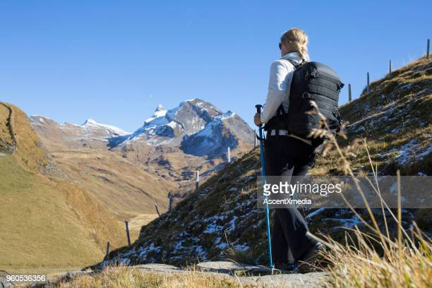 Female hiker descends trail from above Grindelwald, swiss alps