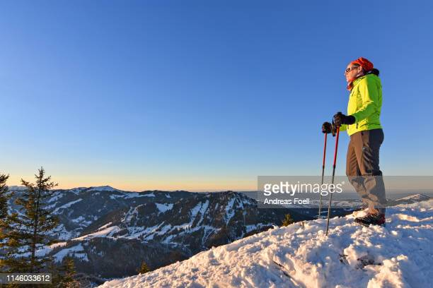 female hiker enjoying sunset in the mountains in winter - andreas solar stock pictures, royalty-free photos & images