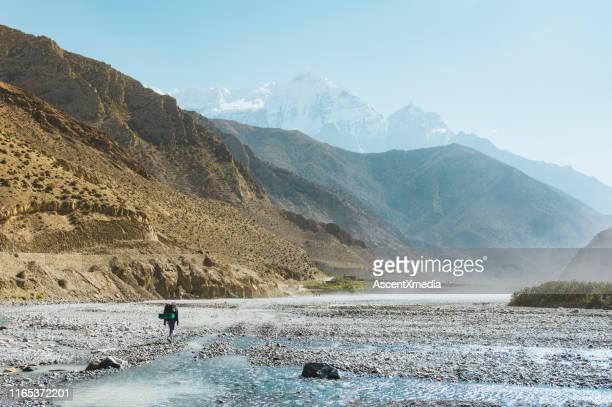 una excursionista explora el escarpado valle de montaña en nepal - emerger fotografías e imágenes de stock