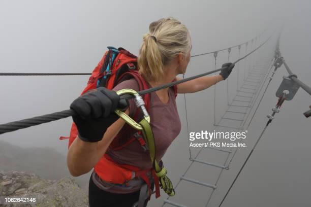 female hiker follows suspension bridge into fog - hängebrücke stock-fotos und bilder