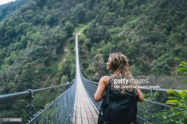 female hiker follows suspension bridge, over gorge - hängebrücke stock-fotos und bilder